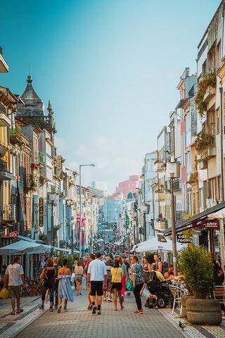 Eine Einkaufsstraße mit Läden und einer Vielzahl an Passanten.